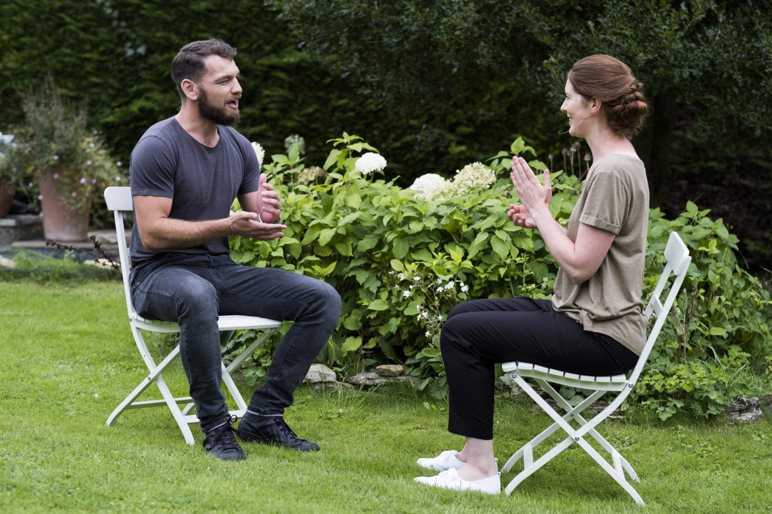 Man and a therapist seated in a garden, talking.